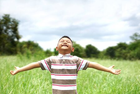 Happy cute little kid boy on green grass lawn on sunny spring or summer day. Little boy dreaming and relaxing on green grass fields. Happy kid with raised arms in green spring field. Happy child stand smiling on green grass fields.