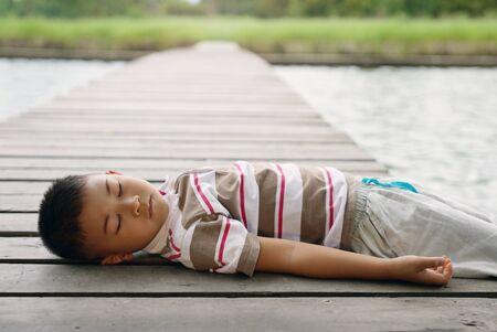 Little boy rest on bridge near the pond in park.Outdoor portrait of boy lying sleep on bridge at park Archivio Fotografico