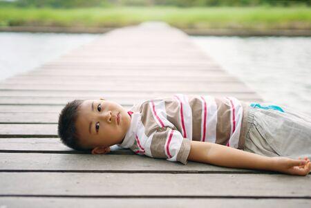 Little boy rest on bridge near the pond in park.