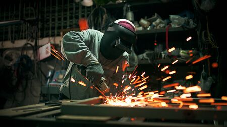 Worker Hard Work Electric Wheel Grinding On Steel Structure in factory. Archivio Fotografico