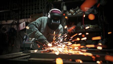 Metal works.Electric wheel grinding on steel structure in factory.