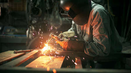 Working person About welder steel Using electric welding machine There are lines of light coming out and safety equipment in factory.