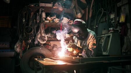 A craftman is welding with workpiece steel.working person about welder steel using electric welding machine there are lines of light coming out and safety equipment in factory industry