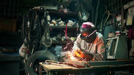 A craftman is welding with workpiece steel.working person about welder steel using electric welding machine there are lines of light coming out and safety equipment in factory industry.