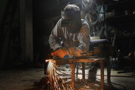The worker cuts the steel with a gas cutter. View from the front. You can see the flames and sparks Archivio Fotografico
