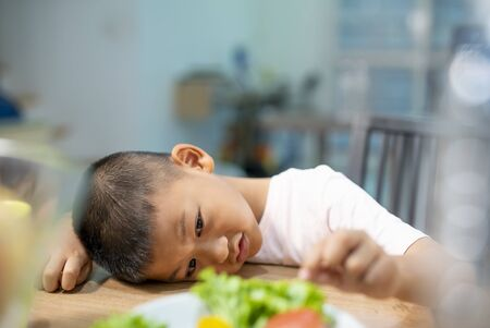 Unhappy little boy eating vegetables or foods at table. Little boy unhappy with his plate of food at table. Archivio Fotografico