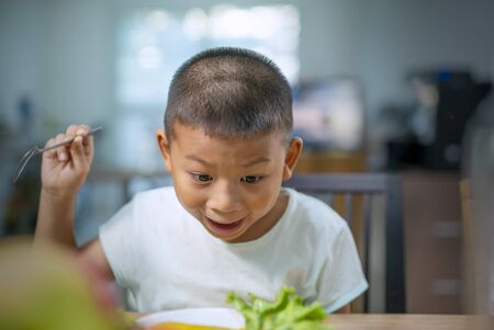 Happy a Boy eating vegetables at home. Healthy nutrition for kids.Cute boy Asian sit at table with plate and food.