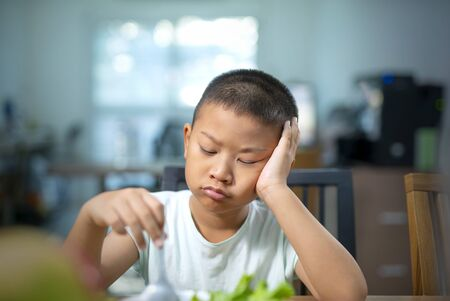 Child is very unhappy with having to eat vegetables. There is a lot of vegetables in his plate. Archivio Fotografico