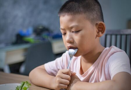 Unhappy little boy eating vegetables or foods at table.