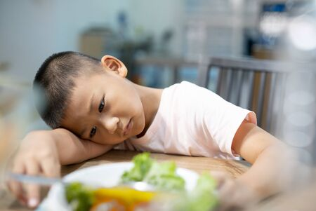 Unhappy little boy eating vegetables or foods at table. Standard-Bild