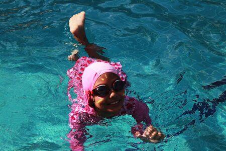 swiming: The girl is swiming in the pool