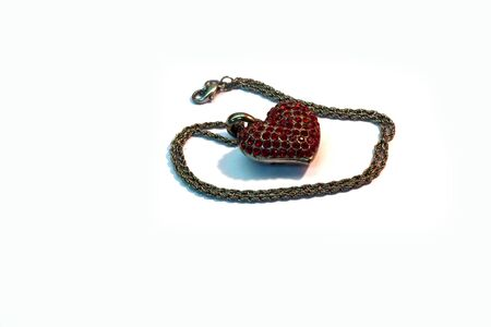 Red heart pendant that is placed on a white background photo