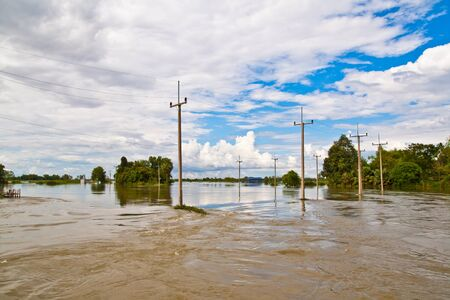 Electricity poles and houses flooded in Thailand photo