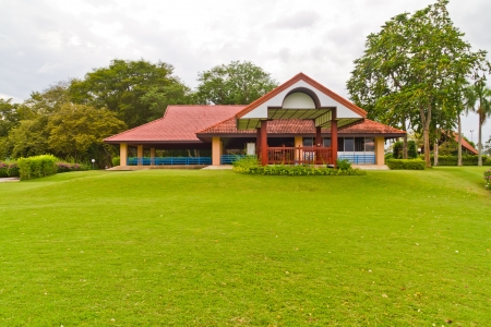Het rode huis op groene gazon in het park