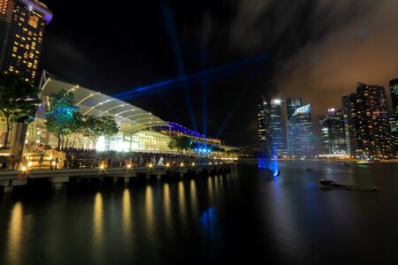 interweaving: The public enjoying the light show at MBS with the city nights cape as the back drop  The light show named Wonder full lasted for 13mins  This is the free showcase of stunning visual effects with interweaving lasers, video projectors and giant streaming w