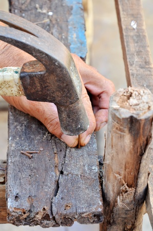 A person hammering a nail into a piece of wood.  Stock Photo
