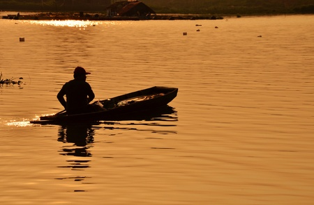 Silhouette of a man rowing in the canoe. photo