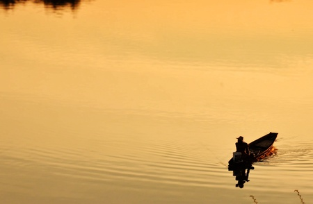 Silhouette of a man rowing in the canoe  photo