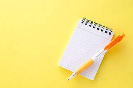 Notepad and pencil on yellow background photo