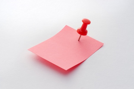 Red note paper with red push pin on white background photo