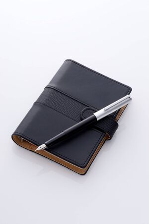 black pocket diary and pen Stock Photo - 12856841