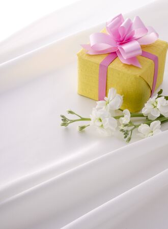 yellow gift box with pink ribbon on white satin photo