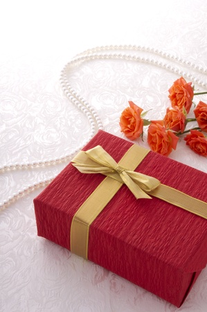 red gift box, red roses and pearl line on the white cloth photo