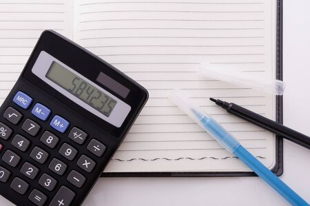 electronic calculator and pens on the notebook Stock Photo - 12856835