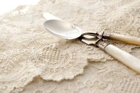 spoon and knife on white lace napkin photo