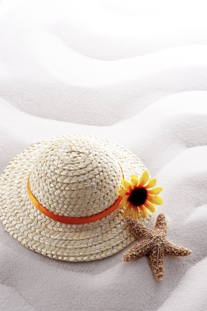 vacationing: starfish and straw hat on white wave sand