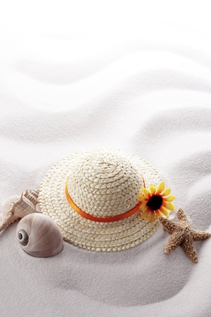 starfish, various shells and straw hat on white wave sand photo