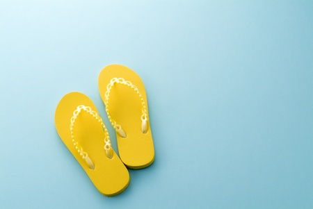 yellow sandals on blue background Stockfoto
