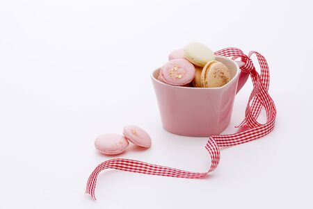 macaroons in pink bowl on white background photo