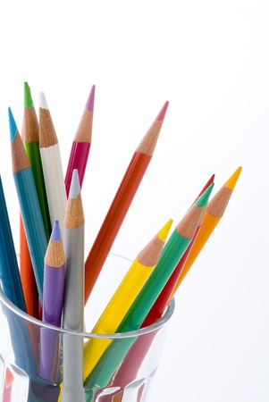 Colored pencils in glass on white background photo