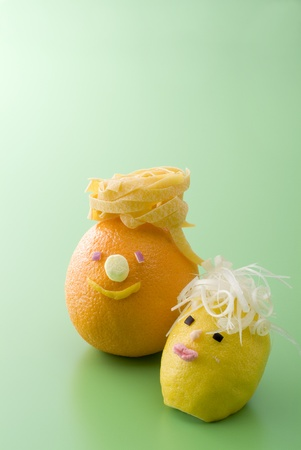 Cute orange and lemon on green background