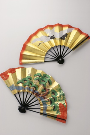 Two of japanese traditional fans designed brace of cranes and pine tree for happy days. 写真素材