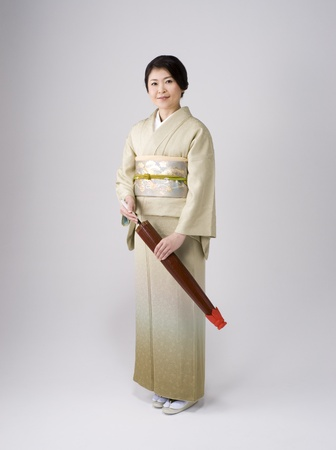 Japanese elegant woman wearing kimono is standing with japanese umblella. photo