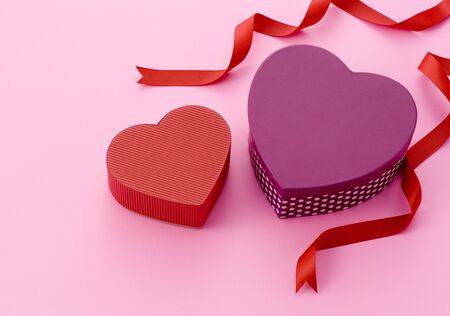 Two of heart-shaped gift boxes and red ribbon on pink background.  photo