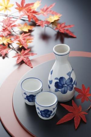 sake: Tazas de sake japonés y una botella en bandejas decoradas con hojas de arce japonés. Foto de archivo