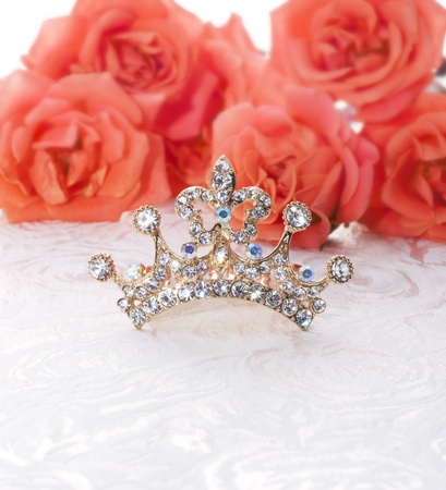 fake diamond: beautiful crown with red roses on lace texture.