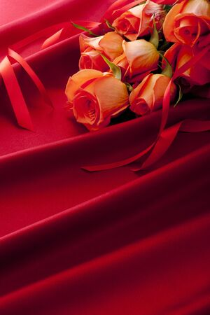 Red rose bouquet with ribbon on the red satin. 写真素材