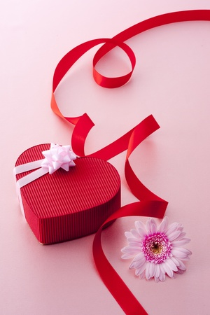Heart-shaped gift box and red ribbon with pink gerbera on pink background.
