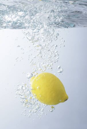 cool backgrounds: A lemon is dropped into water. Stock Photo
