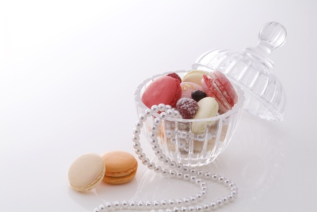 Colorful macaroons in pretty glass container photo