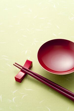 red sake cup and chopsticks on green background