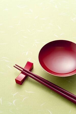japanese sake: taza de sake y los palillos de color rojo sobre fondo verde
