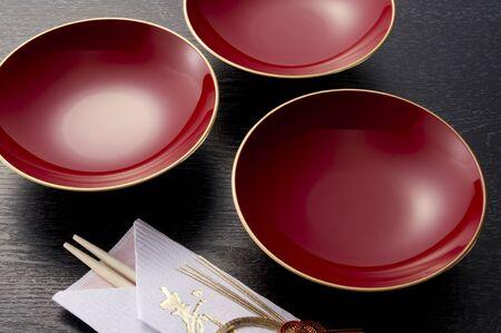red sake cup and chopsticks on black background