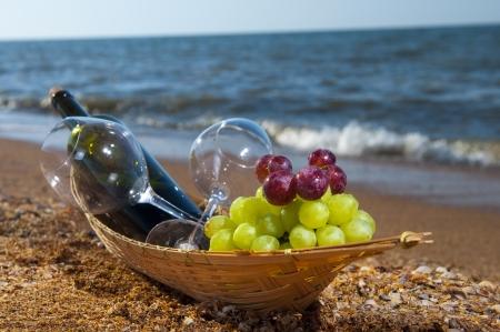 picnic blanket: botle de vino y vasos en la canasta en la playa