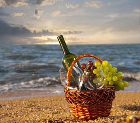 botle of wine and glasses in basket at the beach
