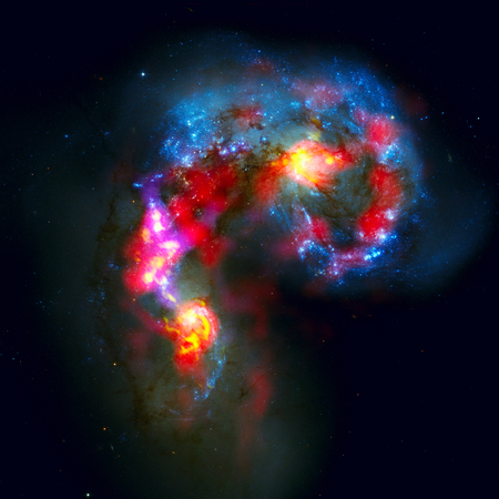 corvus: The Antennae Galaxies, NGC 4038, 4039 are a pair of distorted colliding spiral galaxies in the constellation of Corvus. Elements of this image furnished by NASA. Stock Photo